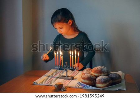 Traditional winter Jewish Hanukkah holiday. Girl lighting candles on menorah for at home. Child celebrating Chanukah festival of lights. Dreidel and Sufganiyot donuts on table. Israel Judaic holiday. Foto stock ©
