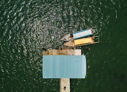 Traditional wooden boat parking in green sea on galang island Batam, Indonesia, aerial view from drone