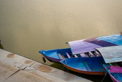 Traditional wooden boats landed at pier on the lakeside. Photographed outdoor with natural light.