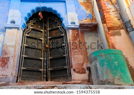 Traditional wooden door and blue coloured house of Jodhpur city, Rajsthan, India. Historically, Hindu Brahmins used to paint their houses in blue for being upper caste, the tradition follows.