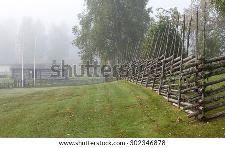 Traditional wooden fence in Nordic countries. Woodwork of bars, sticks to keep the livestock inside. Wooden buildings, left side