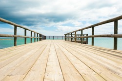 Traditional wooden footbridge  facing  a dramatic ocean setting