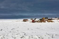 Traditional wooden houses of outport fishing hamlet Joe Batt's Arm at shore of frozen North Atlantic Ocean off Fogo Island, Newfoundland, NL, Canada