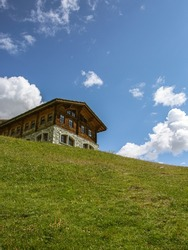 Traditional wooden swiss house in front of a green hil