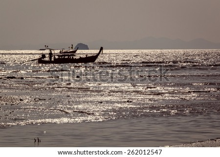Traditional wooden Thai long-tail boat moving at the sea in evening sun near Ao Nang, Thailand