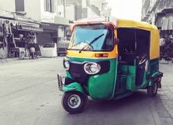 Traditional yellow green tuk tuk taxi on the street. Indian public transport on the streets of new Delhi. Tricycle vintage retro motorcycle
