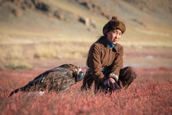 Traditional young kazakh eagle huntress with her golden eagle that is used to hunt for fox and rabbit fur. Ulgii, Western Mongolia.