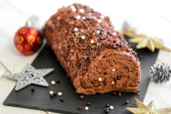 traditional yule log with chocolate and ganache on white background