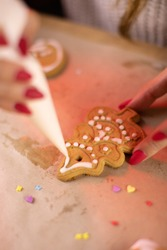 Traditionalist concept. decorating freshly baked Christmas cookies. handmade festive sweets close up. millenials Christmas and New Year traditions. Making handmade festive New Year sweets for gifts