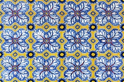 traditionalnational Portuguese tile (azulejo) made with ceramic in varied shapes and colors pattern. Forms of intertwined leaves that create stars, circles and lines in yellow, blue, red and white.