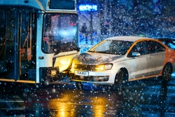 Traffic accident during snowstorm involving taxi car service and  public transport - trolleybus. Taxi car crashed, collision accident at city road. Road accident in blizzard, bad visibility