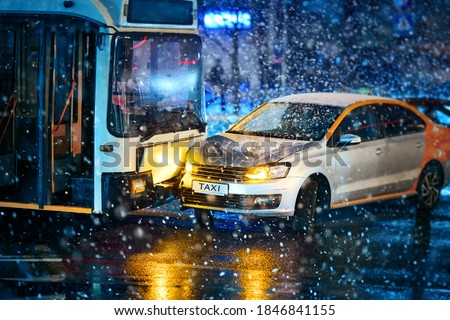 Traffic accident during snowstorm involving taxi car service and  public transport - trolleybus. Taxi car crashed, collision accident at city road. Road accident in blizzard, bad visibility Foto stock ©