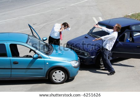 Traffic accident - one driver on the mobile phone, second expressing anger