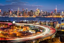 Traffic and light trails on The Helix, a highway loop at the entrance in Lincoln Tunnel. The New York skyline shines in the background.
