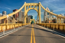 Traffic and people cross the Allegheny River on the Roberto Clemente Bridge in downtown Pittsburgh Pennsylvania USA