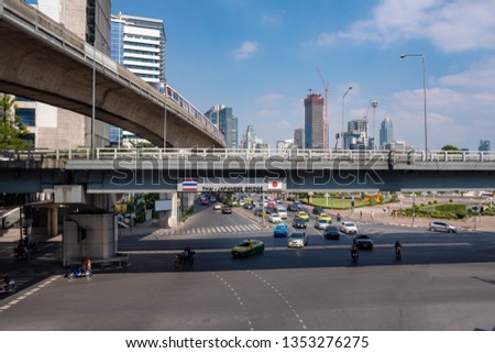 Traffic and transportation in the downtown with commercial building ,sky train and cloudy blue sky background, Bangkok, Thailand #1353276275