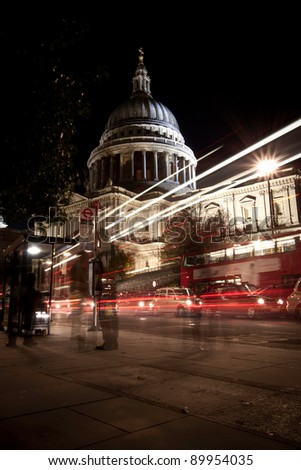 Traffic by St Paul's Cathedral at night, London. Blurred motion of passers-by and traffic.