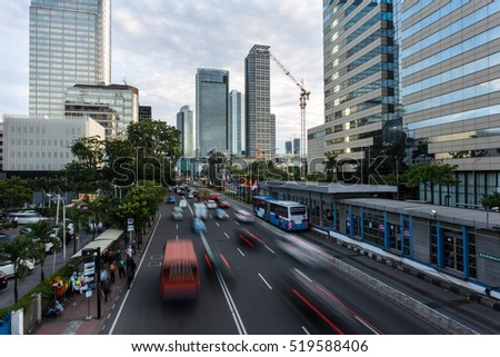 Traffic captured with blurred motion along Jakarta main avenue, Jalan Thamrin, in the business district at dusk in Indonesia capital city.