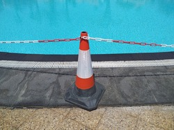 Traffic cone and chain prohibiting passage to the pool. COVID 19 pandemic restrictions. No Trespassing concept.