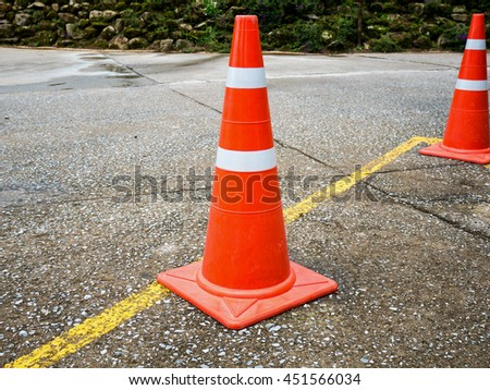 Traffic cone on the asphalt road with yellow line #451566034