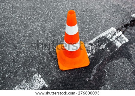 Traffic cone on the asphalt surface with partly rubbed out white road marking line. Close up.