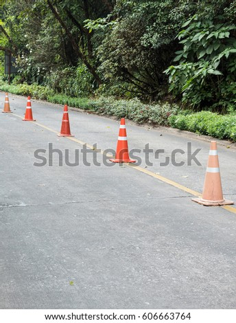 Traffic cone row on the asphalt road near the botanical garden. #606663764