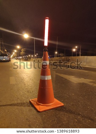 traffic cone with traffic light baton on the road #1389618893