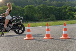 Traffic cones on the moto track. Driving courses or driving licence training. Focus on the orange traffic cones