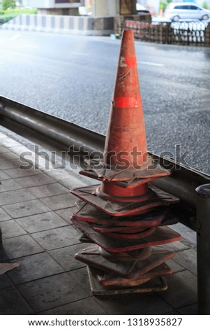 Traffic cones (pylons, witches' hats, road cones, highway cone, safety cones, channelizing devices, construction cones) are used to divert traffic. The reflective sleeves are for nighttime visibility #1318935827