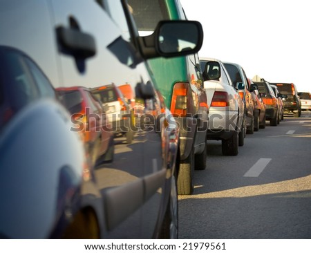 Traffic congestion - a long queue of cars, with reflection of some of the cars in the next lane. Partly isolated on white.