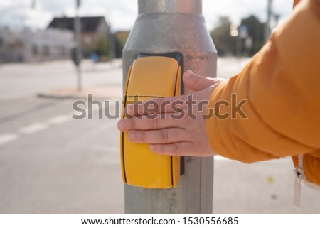 Traffic control. Woman presses a finger on the button for crossing the road #1530556685