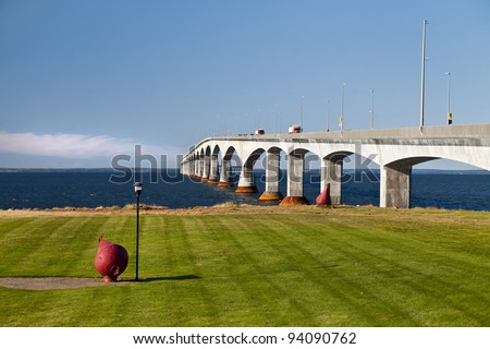 Traffic crossing over the Northumberland Strait from New Brunswick to Prince Edward Island via the Confederation Bridge.  Large red buoy in the foreground.