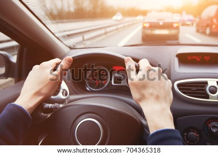 traffic jam, driving car on highway, close up of hands on steering wheel in sunny day #704365318