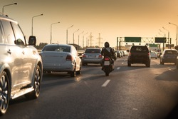 Traffic jam on a hot summer evening. Highway and road junction. Sunset and cars