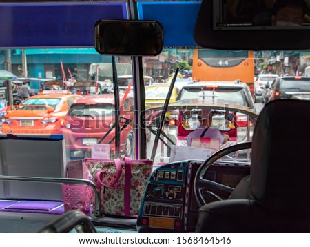 Traffic jam on the streets of Bangkok, view of public bus. A public Bus ride in the metropolis.