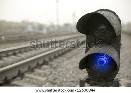 Traffic light at railroad with blue signal is on.