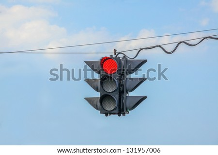 Traffic light on red hanging on wires in the air