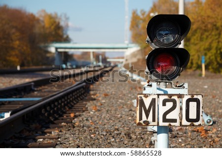 Traffic light shows red signal on railway. Railway station.