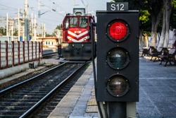 traffic light shows red signal on railway; railway station and the train is coming