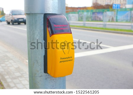 """Traffic light switch button at a pedestrian crossing with the inscription in Russian """"Please touch"""" and """"Please wait."""""""