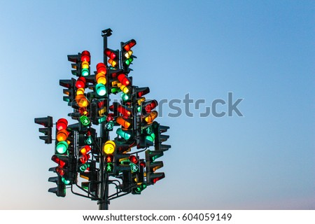 Traffic light tree with a lot of lamps under sky with a sunset. #604059149