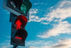 Traffic light with green light for cars and red light for people. Stoplight against blue sky with white clouds, shot with right copy space, traffic concept