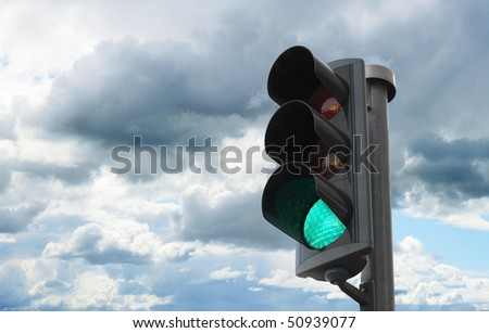 Traffic light with green light lit against sky