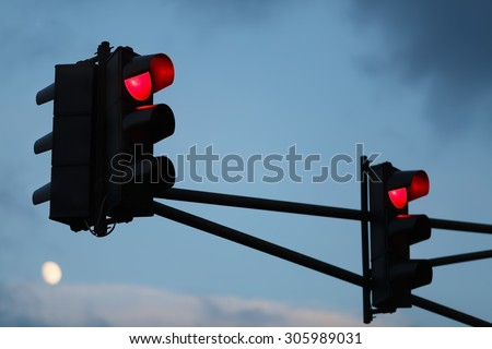 Traffic light with red light against the evening sky. Shallow depth of field. Selective focus. #305989031