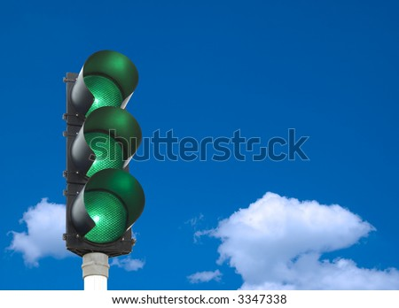 Traffic lights - all three lights are green in front of blue sky