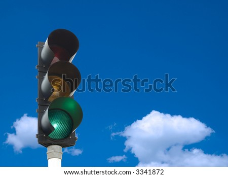 Traffic lights - green light is on - in front of blue sky