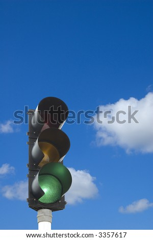 Traffic lights - green light on in front of blue sky