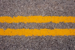 traffic lines view of asphalt from above with two distinct yellow lines gritty urban grungy concrete texture to add text or design artwork, horizontal shot medium closeup