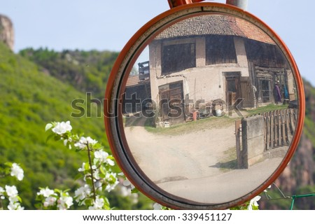 Traffic mirror at complicated countryside street. Old house is reflected in the mirror