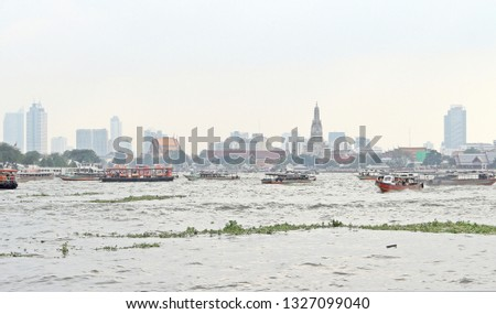 Traffic of transportation by boats in the Choapraya river, major river in Bangkok, Thailand. Taken in front of Wat Arun, Having city view behind as a background. #1327099040